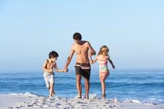 沿海滩儿童父亲运行含沙 免版税图库摄影