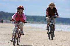 沿海滩女儿母亲骑马 免版税库存照片