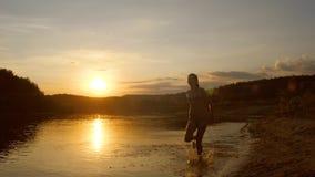 沿海滩的十几岁的女孩奔跑在日落 库存照片