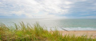 沿海的沙丘在蓝色多云天空下 免版税库存照片
