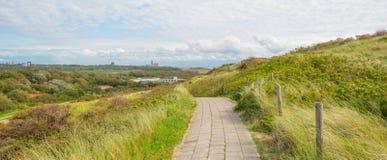 沿海的沙丘在蓝色多云天空下 免版税图库摄影