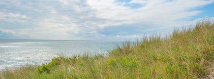 沿海的沙丘在蓝色多云天空下 图库摄影