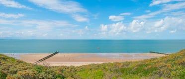 沿海的沙丘在蓝色多云天空下 免版税库存图片