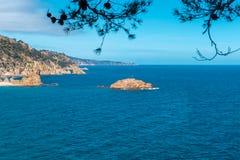沿海的美丽的景色在海震动有加泰罗尼亚旗子的海岛 托萨德马尔,布拉瓦海岸,西班牙 库存照片