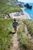 沿海道路的女性远足者 免版税库存图片