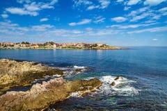 沿海风景-与房子的岩石海滨在与云彩的天空下 库存照片