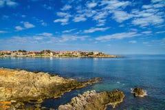 沿海风景-与房子的岩石海滨在与云彩的天空下 免版税库存图片