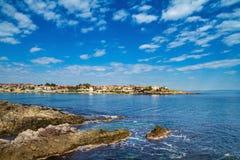 沿海风景-与房子的岩石海滨在与云彩的天空下 免版税库存照片