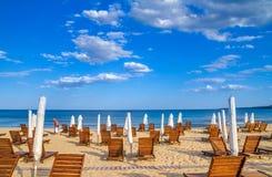 沿海风景-节日的结尾在背景沙滩伞和懒人的 库存图片