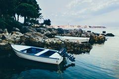 沿海,亚得里亚海 一个木渔船在一个石海浅滩的水中处于低潮中站立在岸附近 库存图片