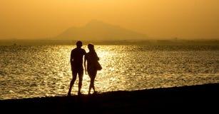沿海滩的浪漫漫步在日落夫妇 库存图片
