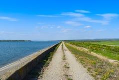沿湖水坝的乡下公路在与完善的天空蔚蓝的一个晴朗的夏日 库存图片