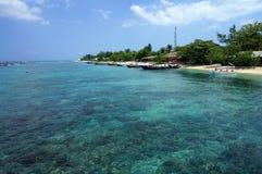 沿热带海滩的透明的绿松石水 库存照片