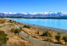 沿特卡波湖和多雪的山在秋天,坎特伯雷,南岛,新西兰的乡下公路 库存图片