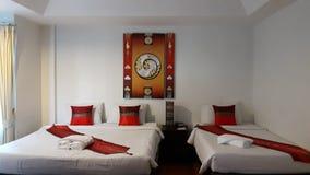 沿白色卧具的三倍室床和有现代艺术温暖的口气的白色红色枕头生动描述在背景的墙壁 免版税库存图片