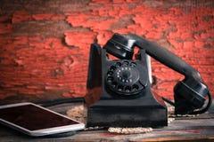沿着片剂计算机的老转台式电话 免版税库存照片