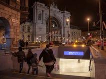 沿着走一个地铁车站的台阶的Amily在布达佩斯Keleti Palyaudvar火车站前面的在晚上 图库摄影