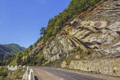 沿着路的陡峭的岩石峭壁 免版税库存照片
