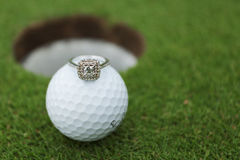 沿着高尔夫球的订婚/婚戒 免版税库存图片