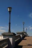 沿石人行桥的街灯反对蓝天 免版税库存图片