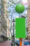 沿离开的路面的空白的绿色广告牌在一晴朗的秋天天 免版税库存照片