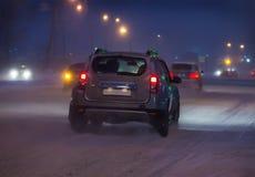 沿积雪的路的汽车驱动 免版税库存照片