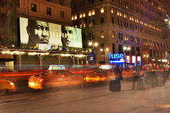 沿纽约的第7个Ave的出租汽车在晚上 免版税图库摄影