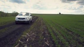 沿肮脏的湿路的白色汽车驱动横跨绿色领域 股票视频