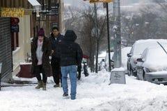 沿街道的人步行在雪风暴期间 免版税库存图片