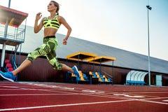 沿踏车的一个女运动员奔跑 体育运动背景 库存照片