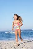沿运行含沙年轻人的海滩女孩 库存图片