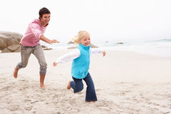 沿追逐女儿父亲冬天的海滩 免版税库存照片