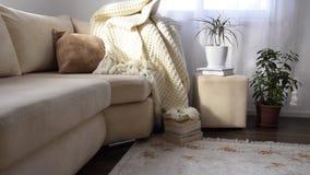 沿邀请舒适的沙发的照相机移动有手工制造羊毛毯子和书的 股票录像