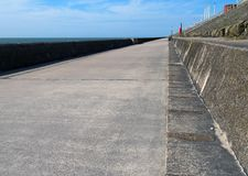 沿防波堤的长的具体人行道在与夏天阳光和海的布莱克浦lancashire 免版税库存照片
