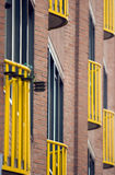 沿阳台砖墙黄色 免版税库存照片