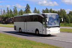 沿高速公路的白色教练公共汽车旅行在夏天 库存照片