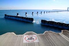 沿冻密歇根湖的没有游泳标志有冰冷的芝加哥地平线岩石和看法的  免版税库存图片