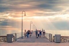 沿Glenelg跳船的人步行在日落 免版税库存照片