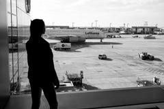 法兰克福,德国- 2015年10月11日:女孩剪影看看在机场的飞机在晴天研了 妇女 免版税图库摄影