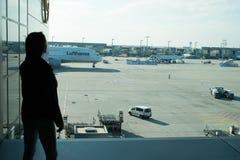 法兰克福,德国- 2015年10月11日:妇女在机场 女孩剪影看看在机场的飞机在晴天研了 T 免版税库存照片