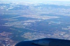 法兰克福,德国- 2017年1月20日, :看法通过在喷气机翼,在积雪的城市的wingview上的航空器窗口  库存照片
