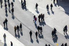 走在有长的阴影的街道的人们 图库摄影