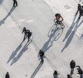 走在有长的阴影的街道的人们 免版税库存图片