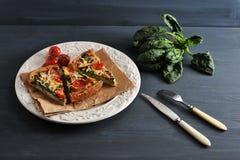 法国乳蛋饼用鸡蛋、新鲜的菠菜、蕃茄和烟肉 库存照片