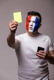 法国全国橄榄球队展示黄牌足球迷在照相机的在灰色背景 库存照片