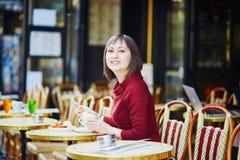法国在室外咖啡馆的妇女饮用的咖啡在巴黎,法国 免版税库存图片