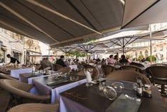 法国室外咖啡馆桌在从太阳的一个机盖下,红葡萄酒 免版税库存图片