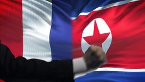 法国对北朝鲜交锋国家相冲突,在旗子背景的拳头 影视素材