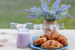 法国新月形面包、小圆面包用葡萄干和蓝莓酸奶在玻璃瓶子在一块蓝色板材 库存图片