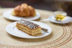 法国新月形面包用茶和蜂蜜 免版税库存图片